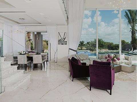 סלון מעוצב במראה מודרני קלאסי עם ספות סגולות ושיש לבן ברצפה